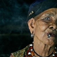 Vietnamese minority woman smoking in her hut